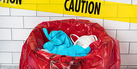 Picture of plastic gloves and face masks in a bin with the word 'Caution' on yellow tape behind it