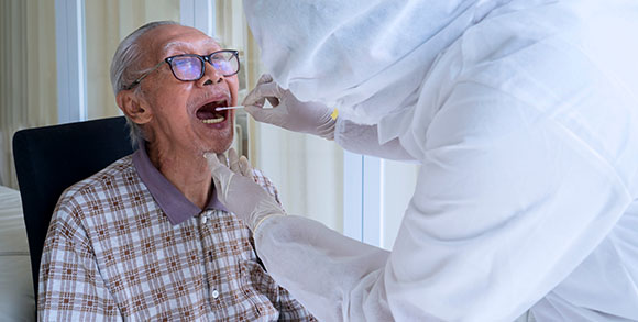 Picture of elderly care home resident receiving oral coronavirus test