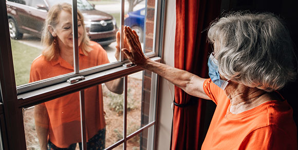 Picture of care home resident lifting her hand to a window to meet the hand of her visitor