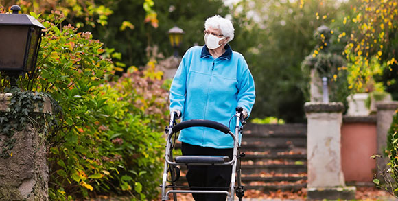 Picture of care home resident wandering through a garden in a care home in the second wave of coronavirus